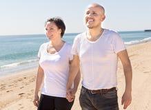 Uomo di mezza età e donna in maglietta bianca che camminano sulla spiaggia fotografia stock