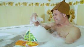 Uomo di mezza età nel bagno che gioca con una barca del bambino stock footage