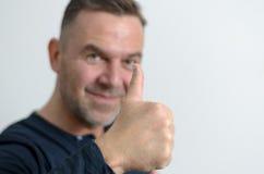 Uomo di mezza età osservato blu che mostra pollice su Fotografie Stock