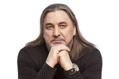 Uomo di mezza età serio con capelli lunghi, primo piano Isolato su una priorità bassa bianca immagini stock