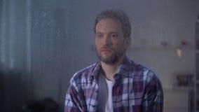 Uomo di mezza età triste solo che guarda attraverso la finestra piovosa, maltempo video d archivio