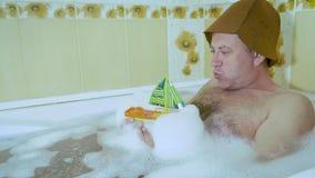 Uomo di mezza et? nel bagno che gioca con una barca del bambino stock footage