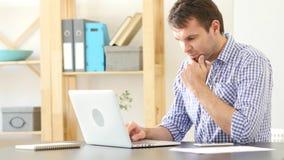 Uomo di pensiero che lavora al computer portatile Fotografia Stock