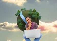 Uomo di pensiero che si siede sul pavimento facendo uso del computer portatile e del sorridere Immagini Stock Libere da Diritti