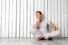 Uomo di pensiero che si siede vicino alla parete Immagine Stock Libera da Diritti
