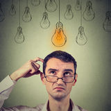 Uomo di pensiero del ritratto in vetri che cerca con la testa di cui sopra della lampadina leggera di idea Fotografia Stock
