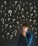 Uomo di pensiero di affari con i punti interrogativi del gesso Immagini Stock