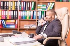 Uomo di pensiero triste nell'ufficio con il microtelefono fotografia stock libera da diritti