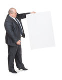 Uomo di peso eccessivo allegro con un segno in bianco Immagini Stock