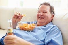 Uomo di peso eccessivo a casa che mangia Chips And Drinking Beer Fotografie Stock Libere da Diritti