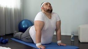 Uomo di peso eccessivo che allunga a casa, posa ascendente del cane del rivestimento, esercizio flessibile della spina dorsale immagini stock libere da diritti