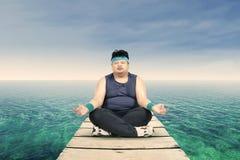 Uomo di peso eccessivo che medita su molo Immagini Stock Libere da Diritti