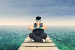 Uomo di peso eccessivo che medita su molo 1 Immagine Stock