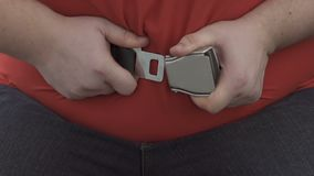Uomo di peso eccessivo che prova a fissare la cintura di sicurezza sulla pancia enorme, comodità in aeroplano stock footage