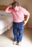 Uomo di peso eccessivo che si pesa sulle scale in camera da letto immagini stock