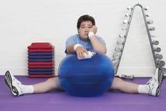 Uomo di peso eccessivo sul pavimento con la palla di esercizio Fotografia Stock Libera da Diritti