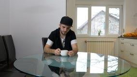 Uomo di postumi di una sbornia nella cucina che prova a svegliare mentre bevendo caffè video d archivio
