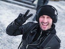 Uomo di Pozitive nel walkink delle cuffie nella via nell'orario invernale Fotografie Stock Libere da Diritti