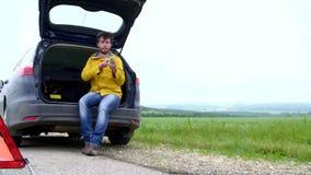 Uomo di rabbia con il suo automobile ripartita con le luci di rischio che provano ad chiamare ma non essere segnale stock footage