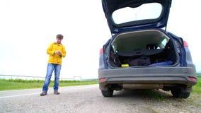 Uomo di rabbia con il suo automobile ripartita con le luci di rischio che provano ad chiamare ma non essere segnale archivi video
