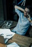 Uomo di refrigerazione che parla sul telefono in ufficio fotografia stock libera da diritti