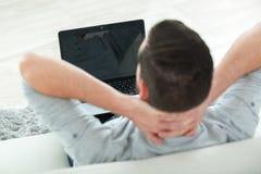 Uomo di retrovisore sul sofà che esamina computer portatile Fotografia Stock Libera da Diritti