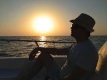 Uomo di rilassamento che si siede sulla barca Fotografie Stock