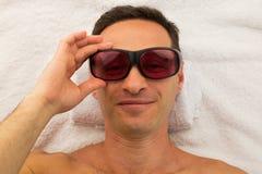 Uomo di rilassamento con i vetri nel salone della stazione termale che mette su asciugamano bianco con la mano Fotografia Stock