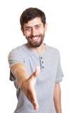 Uomo di risata con la barba che raggiunge mano Immagine Stock
