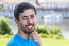 Uomo di risata con la barba e camicia blu su un fiume Fotografia Stock Libera da Diritti