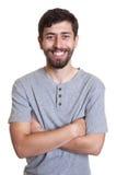 Uomo di risata con la barba e le armi attraversate Fotografia Stock