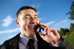 Uomo di risata sul telefono mobile Fotografia Stock