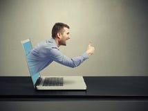 Uomo di risata uscito del computer portatile immagini stock
