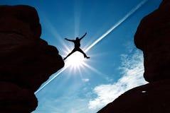 Uomo di salto contro il fondo del cielo di tramonto Immagini Stock
