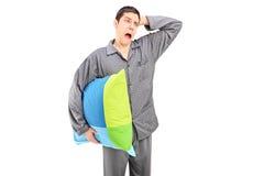 Uomo di sbadiglio in pigiami che tengono un cuscino Immagine Stock Libera da Diritti