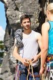 Uomo di scalata di roccia che mostra il nodo della corda della donna Fotografia Stock Libera da Diritti