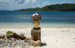 Uomo di scultura di pietra che si siede sulla spiaggia sull'alta stagione di viaggio dell'Indonesia Immagine Stock Libera da Diritti
