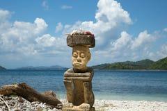 Uomo di scultura di pietra che si siede sulla spiaggia sull'alta stagione di viaggio dell'Indonesia Fotografia Stock Libera da Diritti