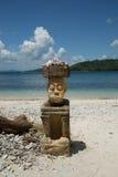 Uomo di scultura di pietra che si siede sulla spiaggia sull'alta stagione di viaggio dell'Indonesia Fotografie Stock