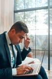Uomo di seduta che esamina lo schermo del computer portatile fotografie stock libere da diritti