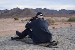 Uomo di seduta che tende fucile Immagine Stock Libera da Diritti