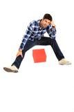 Uomo di seduta con una casella Fotografie Stock Libere da Diritti