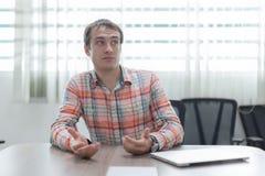Uomo di seduta della scrivania dell'uomo d'affari sconcertante Fotografia Stock