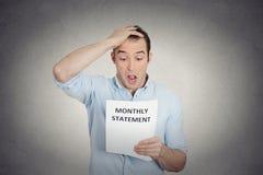 Uomo di sguardo divertente colpito disgustato al suo bilancio mensile corporativo Immagine Stock