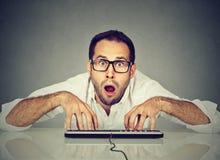 Uomo di sguardo nerd in vetri che scrive sulla tastiera immagine stock libera da diritti