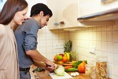 Uomo di sorveglianza della donna cucinare Fotografia Stock