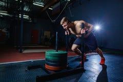 Uomo di spinta della slitta che spinge esercizio di allenamento dei pesi alla palestra Stile adatto dell'incrocio Immagine Stock