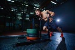 Uomo di spinta della slitta che spinge esercizio di allenamento dei pesi alla palestra Stile adatto dell'incrocio Immagini Stock Libere da Diritti