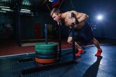 Uomo di spinta della slitta che spinge esercizio di allenamento dei pesi alla palestra Stile adatto dell'incrocio fotografia stock