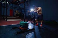 Uomo di spinta della slitta che spinge esercizio di allenamento dei pesi alla palestra Stile adatto dell'incrocio Fotografia Stock Libera da Diritti